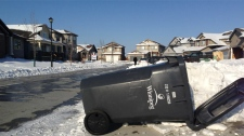 Snow plows knock over garbage carts