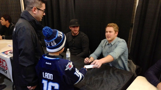 NHL players sign autographs Saturday for young fans before facing off against Winnipeg police officers.