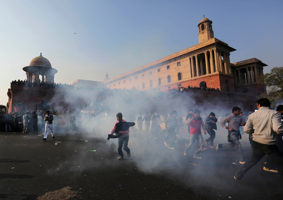 Protesters run from tear gas fired by Indian police as they are driven back from North Block near the Presidential Palace in New Delhi, India, Saturday, Dec. 22, 2012. (AP / Kevin Frayer)