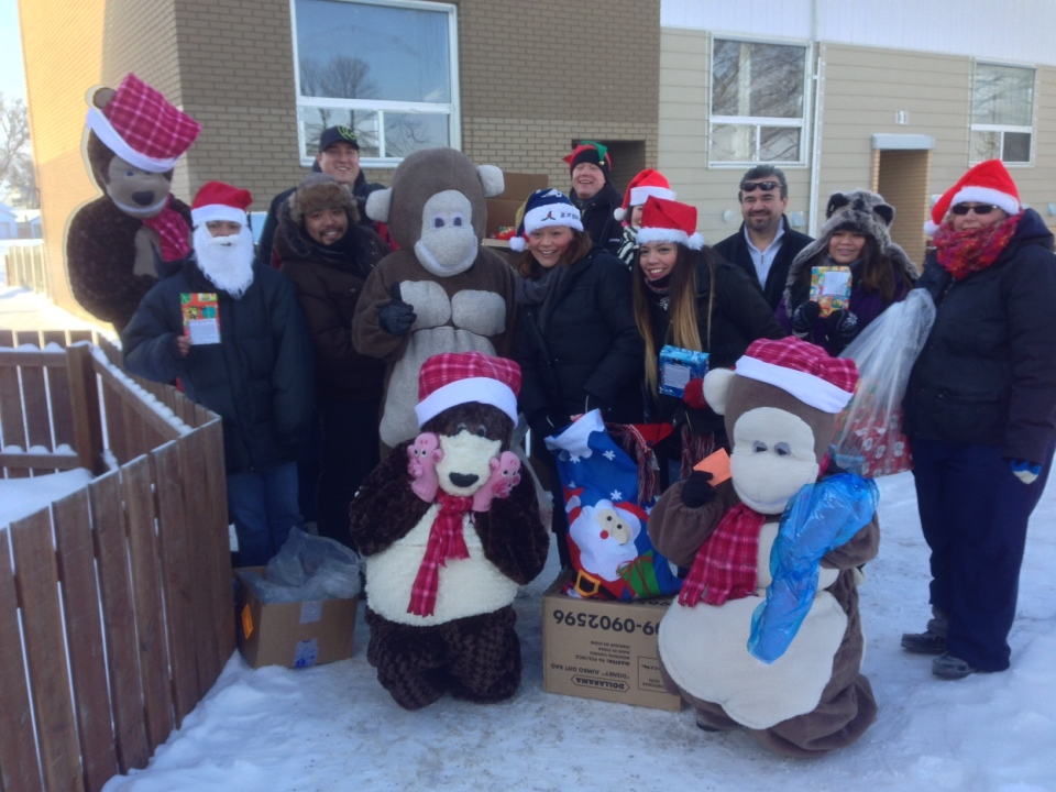 Volunteers pose for a photo after handing out over 1,000 presents to North End residents Sunday.