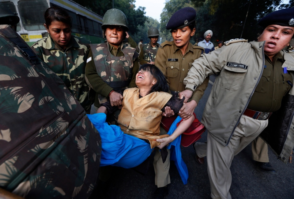 A protester is removed by Indian policemen while protesting against the brutal gang-rape of a woman on a moving bus in New Delhi, India, Tuesday, Dec. 25, 2012. (AP / Saurabh Das)