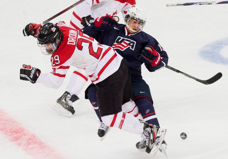 Team Canada forward Jonathan Drouin, left, takes out Team USA forward John Gaudreau, right, during a semi-final game in the world junior hockey championship in Ufa, Russia Thursday. (Nathan Denette / The Canadian Press)