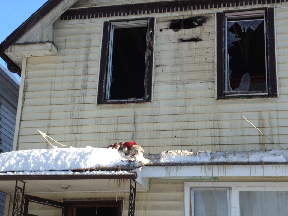 A stuffed animal can be seen by the broken window of a home on Victor Street that caught fire Saturday morning.