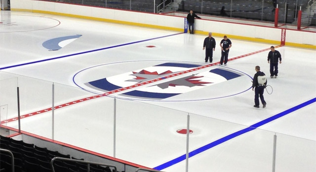 Technicians work on the ice at the MTS Centre in Winnipeg on Jan. 8, 2013.