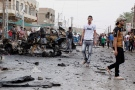Iraqi security forces and civilians inspect the scene of a car bomb attack in the Kamaliyah neighborhood, a predominantly Shiite area of eastern Baghdad, Iraq, Monday, May 20, 2013. (AP Photo/ Hadi Mizban)