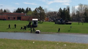 Crews pull a vehicle out of a retention pond in 800 block of Dalhousie Drive in Winnipeg on May 21, 2013.