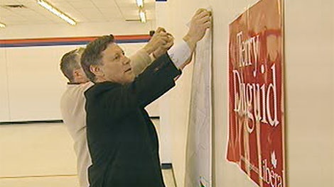 Liberal candidate Terry Duguid hangs a map of Winnipeg South in his campaign office on Friday.
