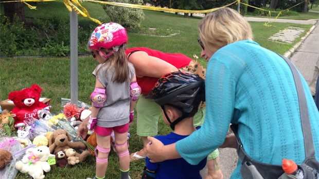 Neighbourhood children Ava and Logan lay flowers and teddy bears on Coleridge Park Drive for two-year-old Anna and three-month-old Nicholas who died in Winnipeg on July 24, 2013.