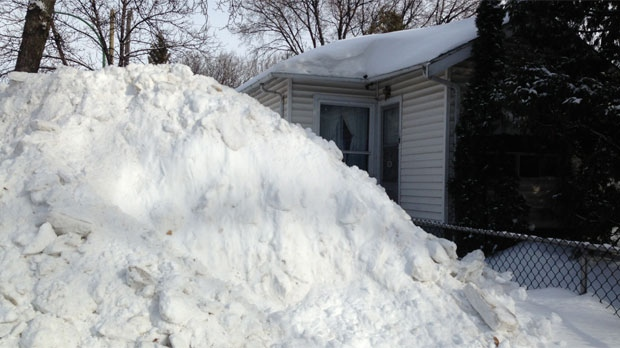 A large snowbank, measuring about 12 feet (3.66 metres), sits on Bannerman Avenue in Winnipeg on Feb. 17, 2014.