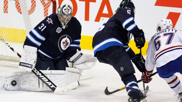 Winnipeg Jets goaltender Ondrej Pavelec (31) gets his pad on Montreal Canadiens forward Max Pacioretty's (67) shot during third period NHL action in Winnipeg on Thursday, December 22, 2011.