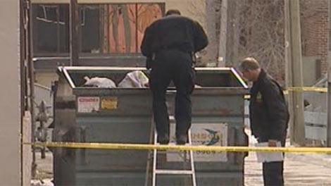 Police examine a dumpster in downtown Winnipeg near Donald and York. People in the area reported seeing something resembling severed hands inside it.