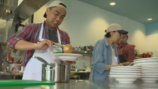 Ryan Lao, a volunteer chef assistant, pours food into a bowl at the NorWest Co-op Community Food Centre, located at 103-61 Tyndall Avenue in Winnipeg, Man.