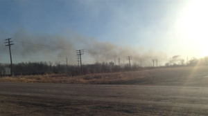 Smoke rises from the grass fire near Wilkes and the Perimeter on April 13, 2015.