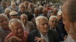 A bank employee orders pensioners to do a queue to enter the bank in numbered order, outside a bank in Athens on July 1, 2015. (AP / Daniel Ochoa de Olza)