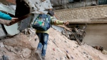 A child navigates through rubble and barbed wire in Aleppo, Syria, Thursday, Feb. 11, 2016. (Alexander Kots / Komsomolskaya Pravda)