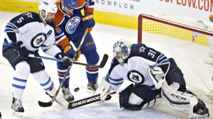 Winnipeg Jets goalie Ondrej Pavelec (31) makes the save on Edmonton Oilers' Zack Kassian (44) as Mark Stuart (5) defends during third period NHL action in Edmonton, Alta., on Saturday February 13, 2016. THE CANADIAN PRESS/Jason Franson