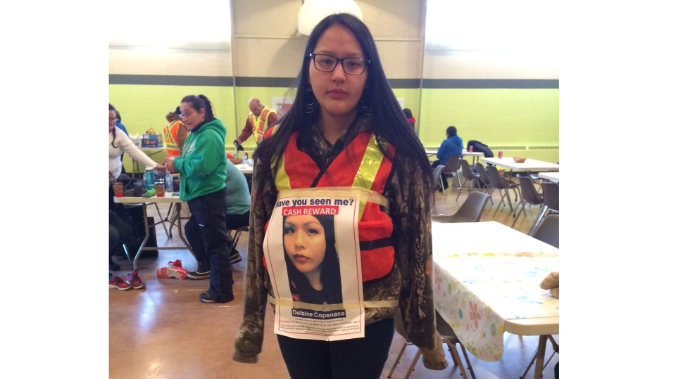 Dayna Copenace, 16, wears a reflective vest with a photo of her twin sister, Delaine, taped on top to avoid mistaken sightings while searching for the missing teen on March 3, 2016.