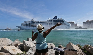 A woman from Cuba waves Adonia leaves port in Miami, Sunday, May 1, 2016, en route to Cuba. After a half-century of waiting, passengers finally set sail on Sunday from Miami on an historic cruise to Cuba. Carnival's Cuba cruises, operating under its Fathom band, will visit the ports of Havana, Cienfuegos and Santiago de Cuba. (Patrick Farrell/The Miami Herald via AP)