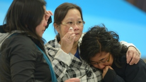 A woman, centre, is greeted by her daughters after arriving in Edmonton from the Fort McMurray area, on Thursday May 5, 2016 (THE CANADIAN PRESS/Jonathan Hayward)