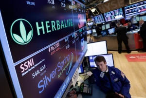 In this Jan. 23, 2014 file photo, specialist Peter Elkins foreground, works at the post that handles Herbalife, on the floor of the New York Stock Exchange.(AP Photo/Richard Drew)