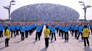 People dance in unison outside of the National Stadium, also known as the Bird's Nest, in Beijing on Saturday, May 21, 2016. (Chinatopix)