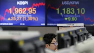 A currency trader watches computer monitors near screens showing the Korea Composite Stock Price Index (KOSPI), left, and the foreign exchange rates between the U.S. dollar and South Korean won, right at the foreign exchange dealing room in Seoul, South Korea on Wednesday, May 25, 2016. (AP / Lee Jin-man)