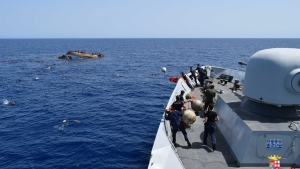 An Italian Navy ship approaches an overturned boat off the Libyan coast, Wednesday, May 25, 2016. (Marina Militare via AP Photo)