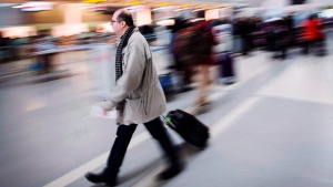 A man carries his luggage at Pearson International Airport in Toronto on December 20, 2013. (THE CANADIAN PRESS/Mark Blinch)