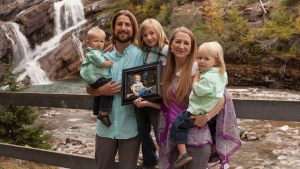 David and Collet Stephan pose with children (left to right) Enoch, 1, Ezra, 8, and Ephraim, 3, while holding a photo of Ezekiel in a family handout photo. (THE CANADIAN PRESS / HO-Jill Calitz)