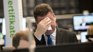 Robert Halver of Baader Bank wipes his face in the trading hall of the Frankfurt, Germany, stock exchange after stocks plummeted when Britain voted to exit from the European Union on Friday morning, June 24, 2016. (Frank Rumpenhorst / dpa)