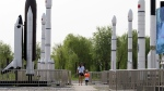 A woman walks with a child as they visit a park with replicas of foreign and domestic space vehicles displayed in Beijing, China, Sunday, June 26, 2016. (AP / Ng Han Guan)