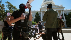 Members of the group called ANTIFA Sacramento (Anti-Fascism Action) try to light a flag on fire as they stage a counter-protest against the Traditionalist Worker Party and the Golden State Skinheads at the California state Capitol in Sacramento, Calif., Sunday, June 26, 2016 (Paul Kitagaki Jr. / The Sacramento Bee via AP)