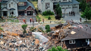 Firefighters and emergency personal work at the scene after a home explosion happened in Mississauga, Ont., on Tuesday, June 28, 2016. (THE CANADIAN PRESS/Nathan Denette)