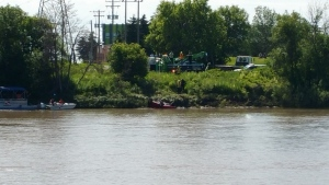 Tow trucks pull a red vehicle from the Red River near the Fort Garry Bridge on Friday. Police were called to the area around 2:15 p.m. on Thursday when passersby thought they saw something in the water.