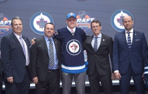 Patrik Laine, second overall pick, stands on stage with members of the Winnipeg Jets management team at the NHL draft in Buffalo, N.Y., on June 24, 2016. No. 2 overall draft pick Patrik Laine signed a three-year entry-level contract with the Winnipeg Jets on Sunday.The deal is worth an average annual value of $3.575 million which includes $2.65 million in bonuses. THE CANADIAN PRESS/Nathan Denette