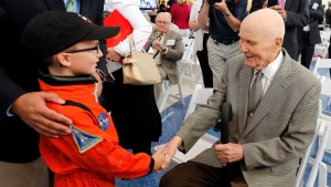 In this June 28, 2016, file photo, former astronaut and U.S. Sen. John Glenn, D-Ohio, right, shakes hands with 8-year-old Josh Schick, left, before an event to mark the September 2016 renaming of Port Columbus International Airport to John Glenn Columbus International Airport in Columbus, Ohio. (Jay LaPrete, File/AP Photo)