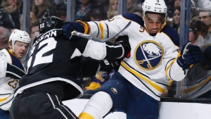 Los Angeles Kings defenceman Luke Schenn, left, checks Buffalo Sabres left wing Evander Kane against the boards during the first period of an NHL hockey game Saturday, Feb. 27, 2016, in Los Angeles. THE CANADIAN PRESS/AP/Danny Moloshok