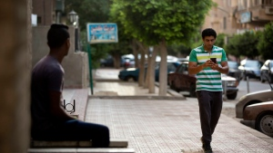"In this Wednesday, July 20, 2016 photo, Egyptian dentist Mark Shehata, 24, uses the ""Pokemon Go,"" mobile phone application while walking in Cairo, Egypt. (Amr Nabil/AP Photo)"