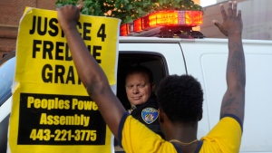 Melvin Townes of Baltimore stands with a 'Justice 4 Freddie Gray' sign in front of a police officer on July 8, 2016. (Caitlin Few / The Baltimore Sun via AP)