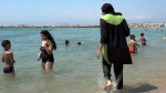 n this Aug. 4 2016 file photo made from video, Nissrine Samali, 20, gets into the sea wearing a burkini, a wetsuit-like garment that also covers the head, in Marseille, southern France. Burkinis vs. bikinis. Beneath the clash over how to dress, or undress, on the beaches of France simmers an issue that for decades has divided the nation, and grown more complex in this time of terrorism.(AP Photo, File)