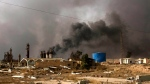 In this Sunday, August 28, 2016 photo, Oil wells on the edge of Qaraya Sunday August 28, 2016 burn days after the key town south of was retaken from the Islamic State group by Iraqi ground forces backed by U.S.-led coalition airpower. (Susannah George/AP)