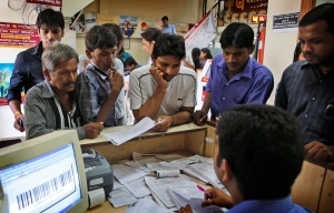 In this file photo, Indians gather around a table inside a state-owned bank in New Delhi, India, Thursday, Aug. 28, 2014. (AP / Manish Swarup)