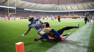Winnipeg Blue Bombers' Clarence Denmark, front, scores a touchdown as B.C. Lions' Chandler Fenner, back, defends during the second half of a CFL football game in Vancouver, B.C., on Friday October 14, 2016. (The Canadian Press/Darryl Dyck)