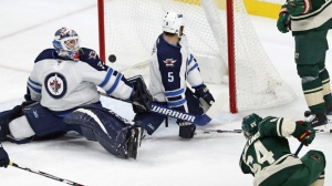 A shot on goal by Minnesota Wild's Mikael Granlund, right, of Finland, misses the net as Winnipeg Jets goalie Michael Hutchinson, left, and Mark Stuart defend in the first period of an NHL hockey game Saturday, Oct. 15, 2016, in St. Paul, Minn. (AP Photo/Jim Mone)