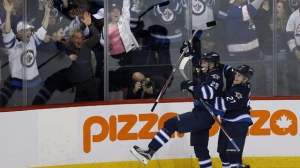 Winnipeg Jets' Nikolaj Ehlers (27) and Patrik Laine (29) celebrate Laine's game-winning goal and hat-trick during overtime against the Toronto Maple Leafs in NHL action in Winnipeg on Wednesday, Oct. 19, 2016. (The Canadian Press/John Woods)