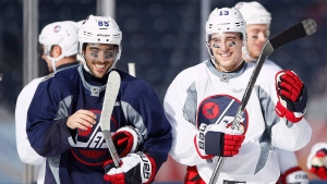 Winnipeg Jets' Mathieu Perreault (85) and Brandon Tanev (13) during practice at Investors Group Field in preparation for the NHL Heritage Classic in Winnipeg on Saturday, October 22, 2016. (THE CANADIAN PRESS/John Woods)