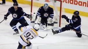 Nashville Predators' Ryan Johansen (92) fires a shot on Winnipeg Jets goaltender Connor Hellebuyck (37) between Josh Morrissey (44) and Brandon Tanev (13) during third period NHL hockey action in Winnipeg, Sunday, November 27, 2016. THE CANADIAN PRESS/Trevor Hagan