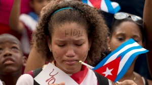 A school girl cries as schoolmates sing songs as they wait for the caravan driving the ashes of Cuba's leader Fidel Castro at the Cespedes Park in Santiago, Cuba, Saturday, Dec. 3, 2016. After a four-day journey across the country through small towns and cities where his rebel army fought its way to power nearly 60 years ago, his remains will be interred in Santiago on Sunday.(AP Photo/Ricardo Mazalan)