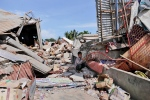 A boy sits on the rubble of a building that collapsed after an earthquake as he takes shelter from the sun in Pidie Jaya, Aceh province, Indonesia, Wednesday, Dec. 7, 2016. (AP Photo/Heri Juanda)