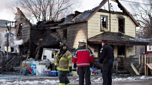 Firefighters survey the damage to a home in Port Colborne, Ontario, where a fire broke out overnight, leaving one person dead and three others who are believed to be part of the same family unaccounted for, on Wednesday, December 14, 2016. THE CANADIAN PRESS/Aaron Lynett